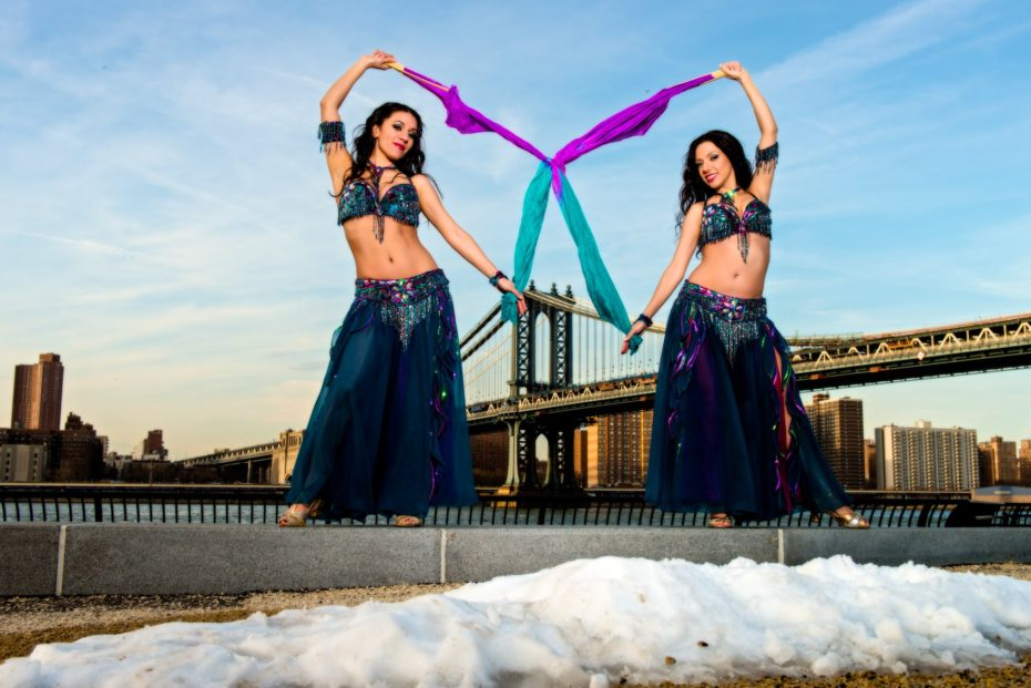 Belly dance Sira NY in a spirited moment with sister bellydancer Tava. The two belly dancers are wearing identical costumes.