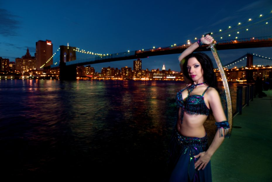 Sira wields a mystical bellydance sword at night in front of the city skyline