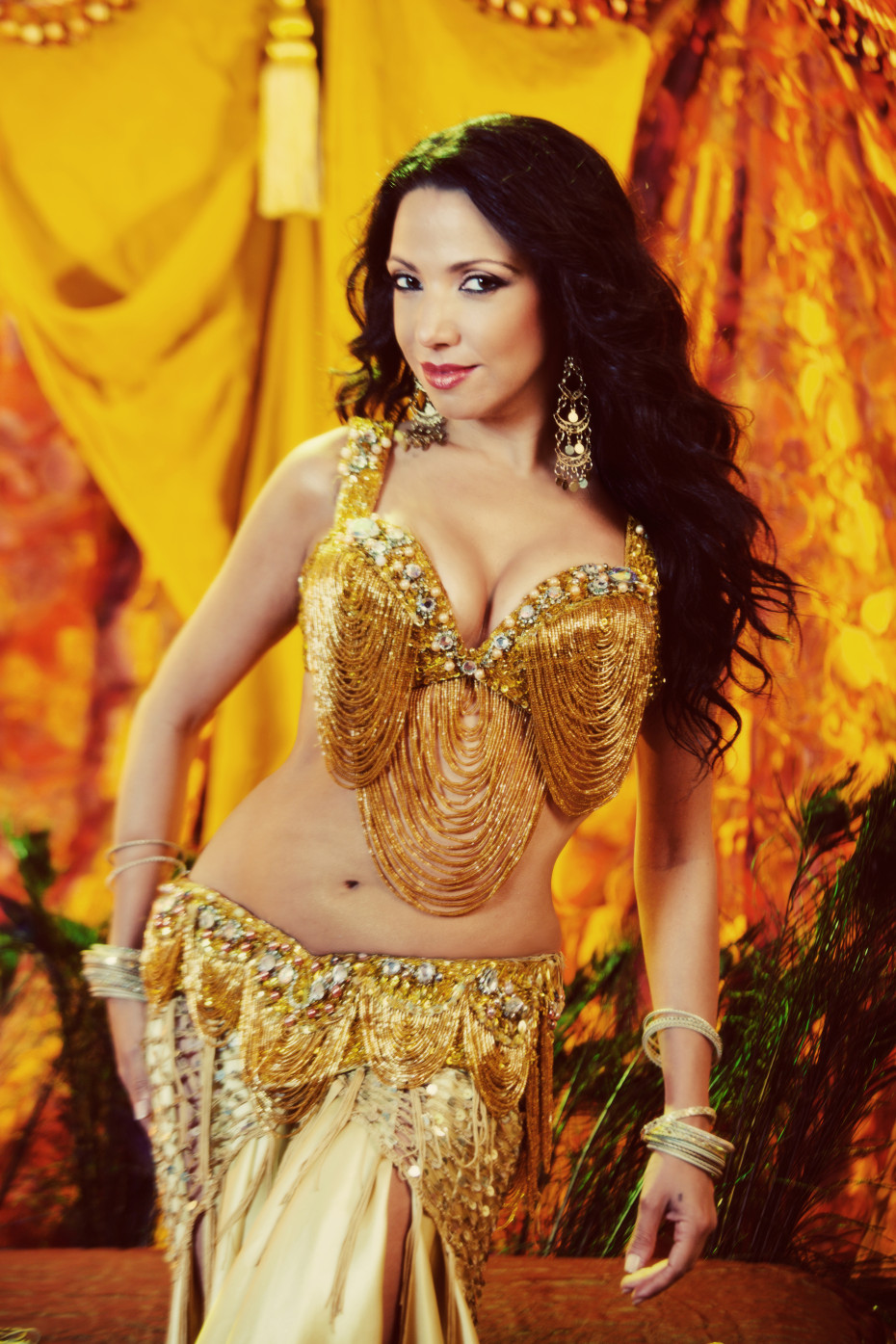 Sira in a luscious gold bellydance costume, dripping with gems and fringe.