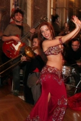 Sira performs in a red belly dance skirt to live music by Balkan Beat Box