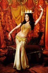 Sira balances a candle tray on her head. She is wearign a gold belly dance costume