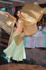 Sira makes a dramatic gesture on the dancefloor of a wedding reception in a banquet hall