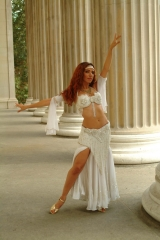 Sira, the New York belly dancer, poses daintily in from of Roman columns. Her head is tilited slightly and she wears a sparkling white costume