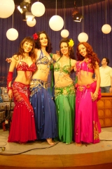 Sira and her belly dancer friends pose happily on the set of the Conan Obrian. They have their arms around each other and are wearing brightly colored dresses