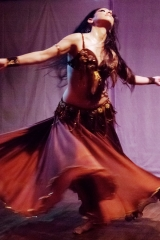 Sira's long bellydance skirt flares out as she dances across the stage in a theater show