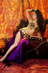 Sira NY embodies the classic feminine archetype of a true belly dancer. She is reclining in a royal purple costume