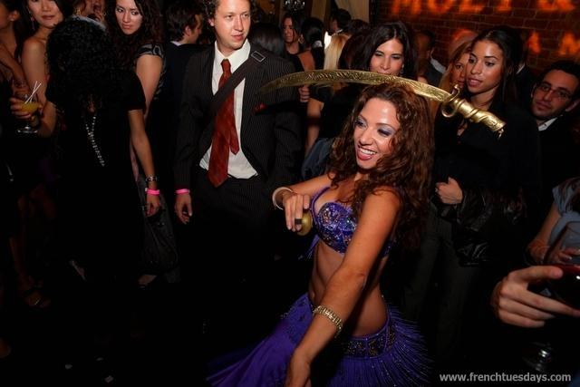 A crowd of happy guests looks on as Sira balances a sword on her head during a bellydance performance