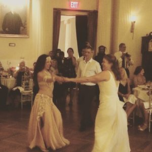 Sira, a belly dancer, encourages a bride to join her on the dancefloor surign the wedding reception