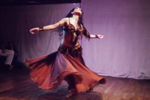 Sira whirls onstage, wearing a long flowing skirt and beaded fringe